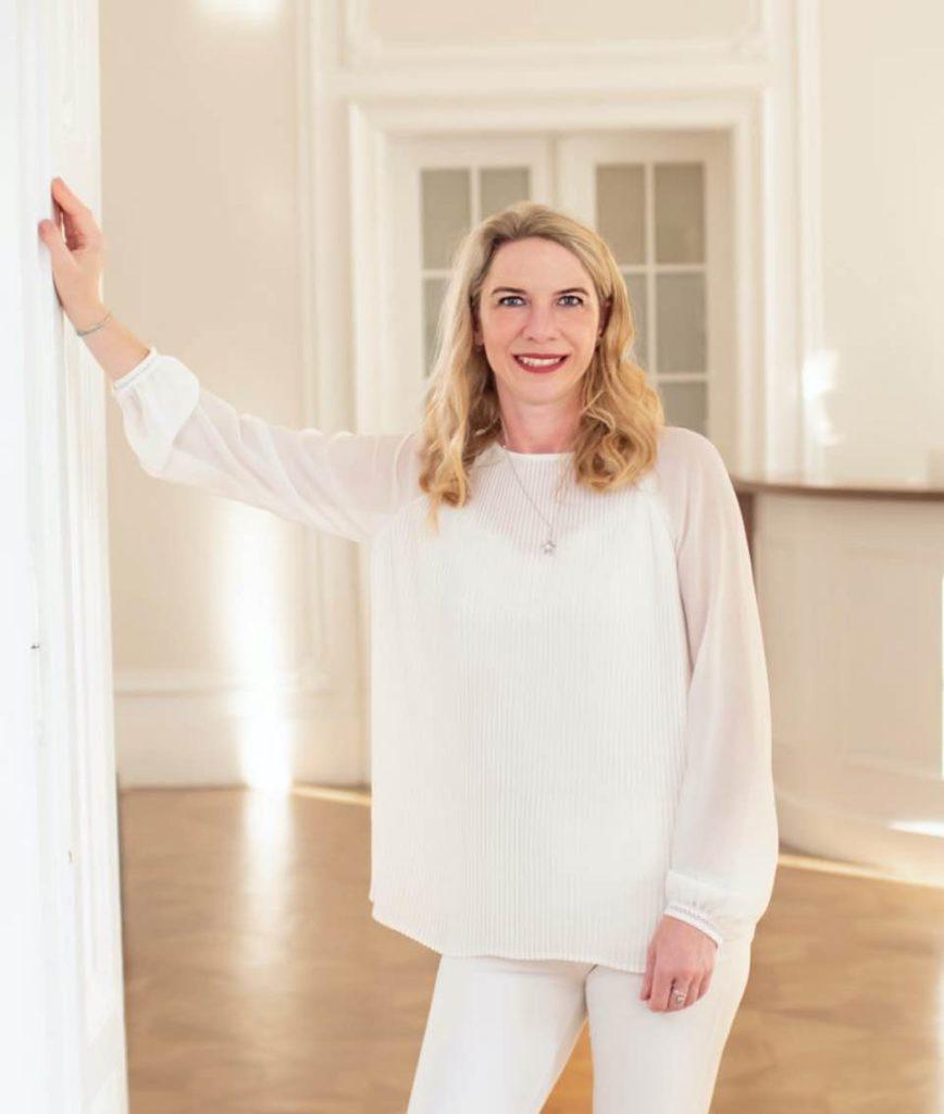 Dr. Manuela Weninger lächelt und lehnt min einer Hand am Eingang ihrer Praxis